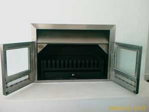 Mildsteel insert fireplace with stainless trim and doors